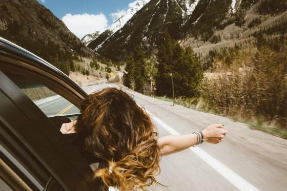 Mulher viajando de carro com o braço para fora da janela