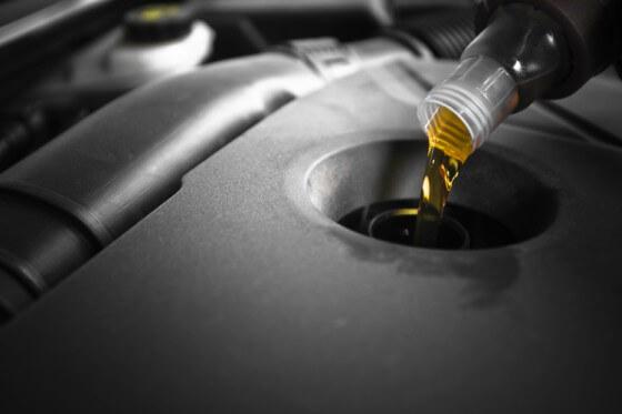 Na imagem, óleo sendo despejado em motor de carro
