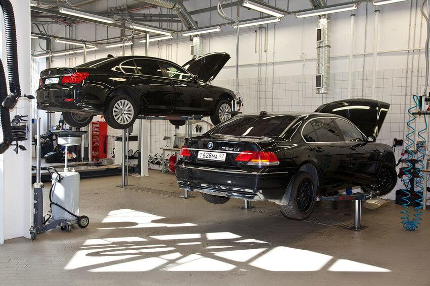 Dois carro BMW em processo de revisão em centro automotivo