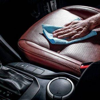 Mão higienizando banco de couro carro